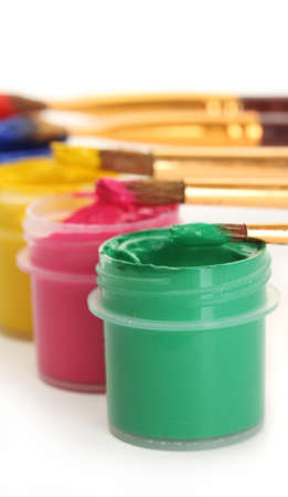 brushes on the jars with colorful gouache on white background close-up photo
