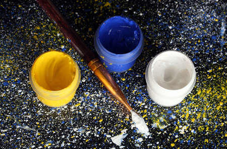 Jars with colorful gouache and brush on black background, spattered with colorful paint close-up photo