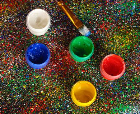 spattered: Tarros con gouache colorida y pincel sobre fondo negro, salpicado de pintura colorida primer plano