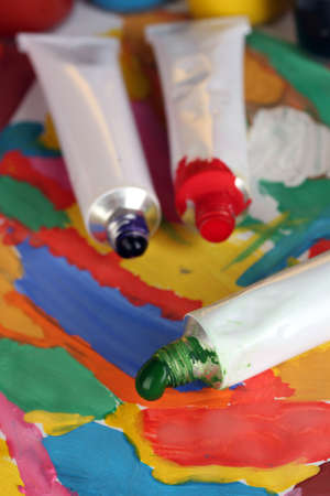 tubes with colorful watercolor on colorful image close-up photo
