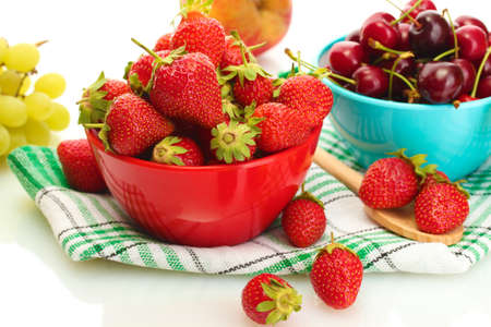 Ripe strawberries and cherry berries in bowls, grapes and apple isolated on white photo
