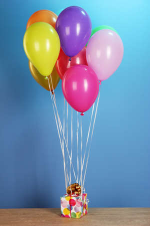 colorful balloons holding a gift on a wooden table on a blue background photo