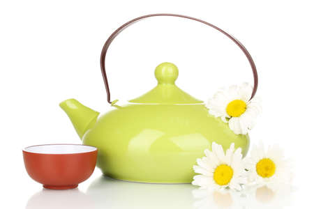 Teapot and cup with chamomile tea isolated on white photo