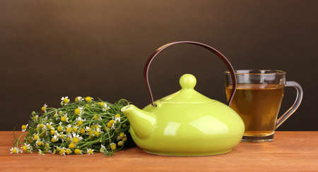Teapot and cup with chamomile tea on wooden table on brown background photo