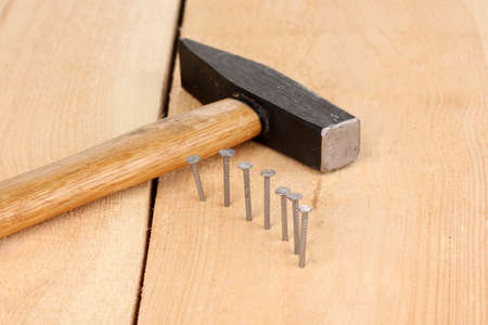 split rail: Metal nails in wooden plank and hammer Stock Photo