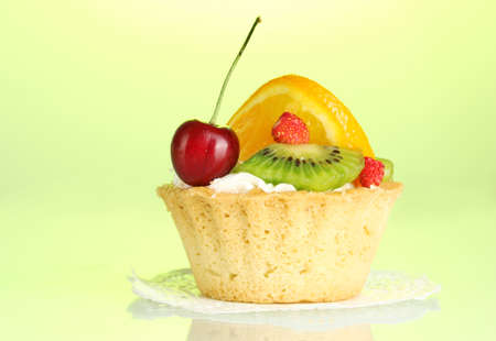 sweet cake with fruits on green background photo