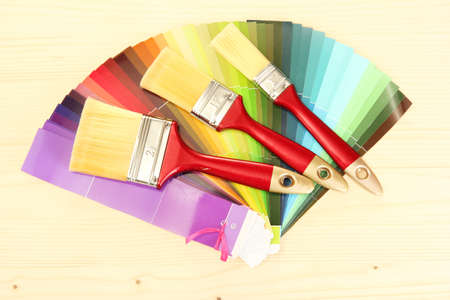 paint brushes and bright palette of colors on wooden background photo