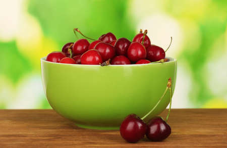 cherry in green bowl on wooden table on green background photo