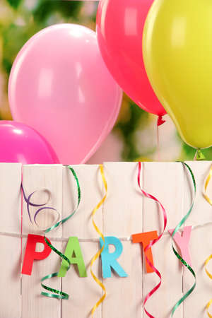 party balloons: Party. Balloons against a wooden fence on green background Stock Photo
