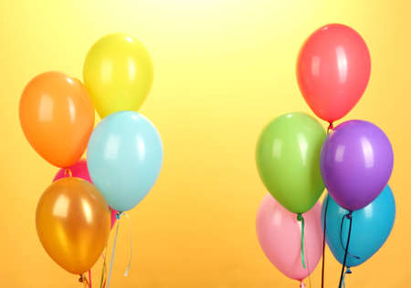 balloon background: colorful balloons on yellow background close-up Stock Photo