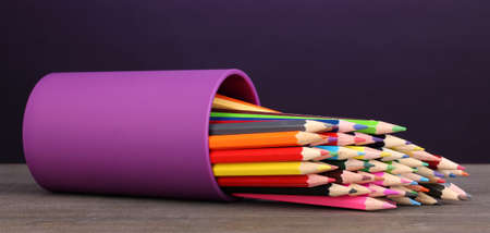 Color pencils in glass on wooden table on violet background photo