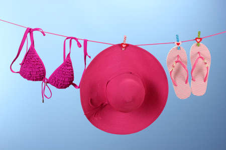 Womens bra swimsuit, hat and flip-flops hanging on a rope on blue background photo