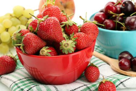 Ripe strawberries and cherry berries in bowls, grapes and apple close up Stock Photo - 14042015