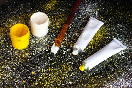 spattered: Frascos con gouache blanco y amarillo, cepillo y tubos con acuarela blanco y amarillo sobre fondo negro, salpicado con pintura blanca y amarilla de cerca