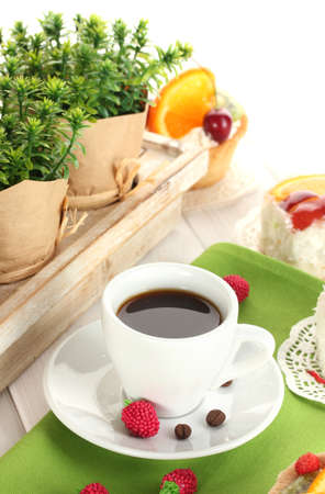 cup of coffee and sweet cakes with fruits on wooden table photo