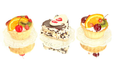 sweet cakes with fruits and chocolate isolated on white photo