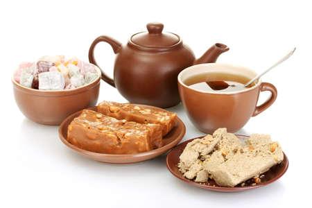 confect: Teiera con tazza e piattino con i dolci orientali - Turkish Delight, sorbetto e halva isolato su bianco Archivio Fotografico