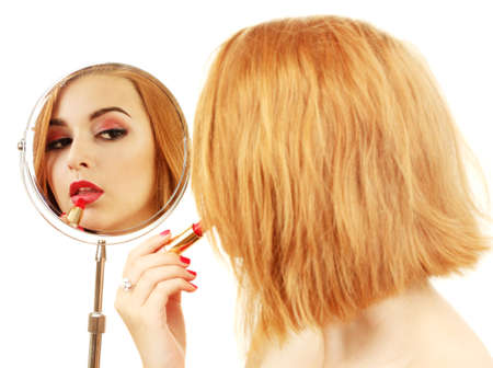 beautiful woman is applying her lips with red lipstick, she is looking at the mirror photo