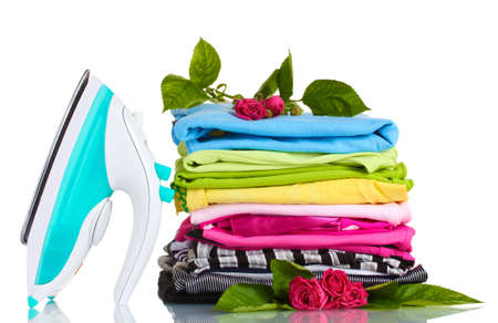 Pile of colorful clothes and electric iron with roses isolated on white photo