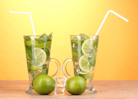 Glasses of cocktail with lime and mint on wooden table on yellow background photo