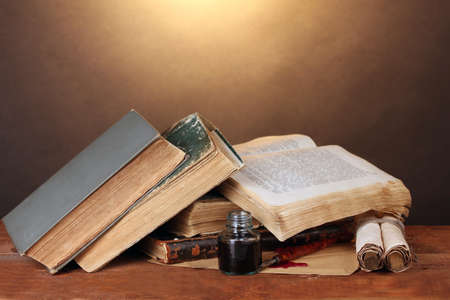 old books, scrolls, ink pen and inkwell on wooden table on brown background photo