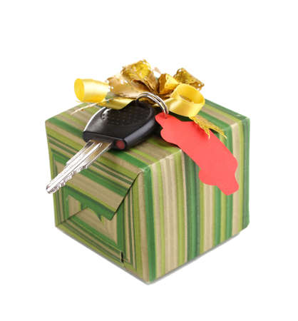 Car key with charm on gift box isolated on white photo