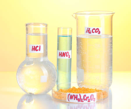 Test-tubes with various acids and chemicals on yellow background photo