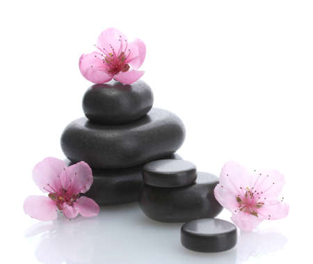 Spa stones and pink sakura flowers isolated on white  photo