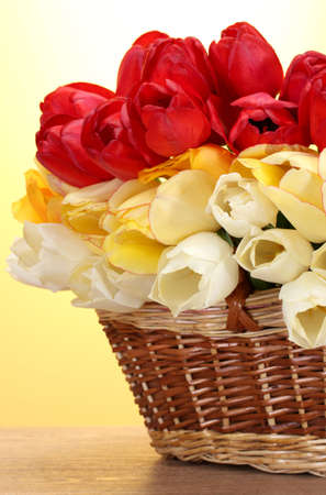 beautiful tulips in basket on wooden table on yellow background  photo