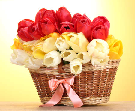 beautiful tulips in basket on wooden table on yellow background Stock Photo - 14033756