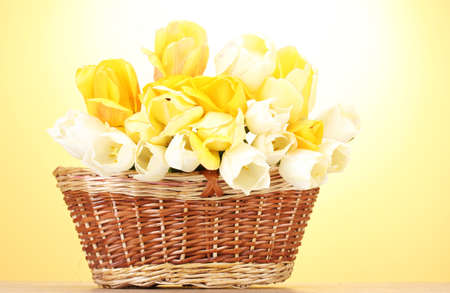 beautiful tulips in basket on wooden table on yellow background Stock Photo - 14033748