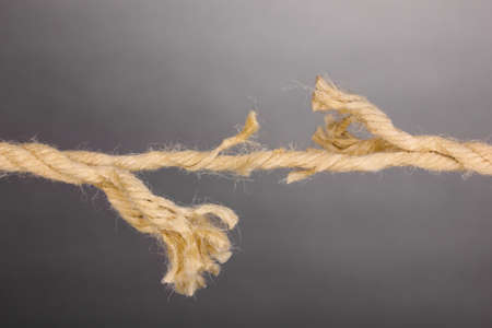 discontinuity: Breaking rope on grey background