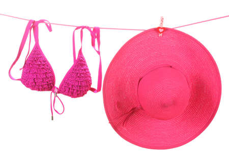 Womens bra swimsuit and hat hanging on a rope on white background photo