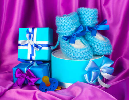 blue baby boots, pacifier, gifts on silk background  photo