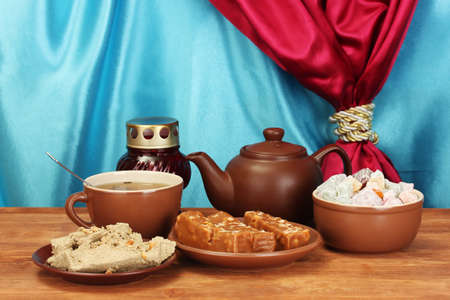 confect: Teapot with cup and saucers with oriental sweets - sherbet, halva and turkish delight on wooden table on a background of curtain close-up