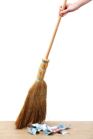 Broom sweep the euro on white background close-up photo