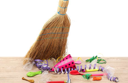 Broom sweep the trash after a party on white background close-up Stock Photo