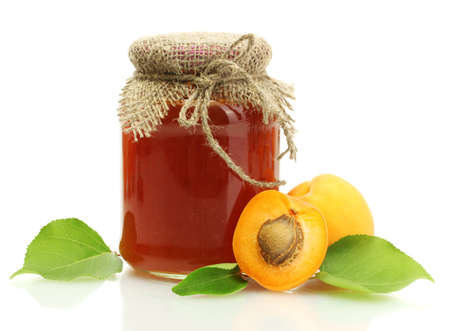 Apricot jam in a jar and sweet apricots isolated on white photo