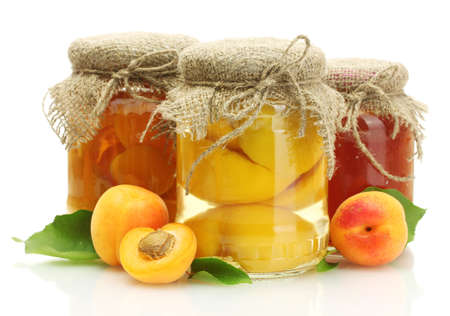 canned apricots and jam in a jars with sweet apricots isolated on white photo