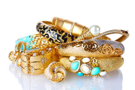Beautiful golden bracelets and rings isolated on white photo