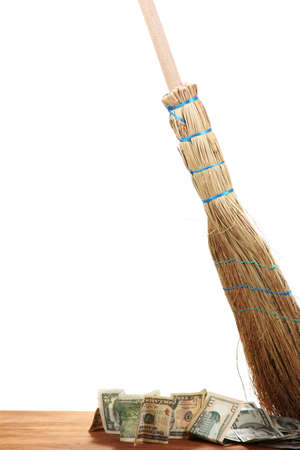 Broom sweep the dollars on white background photo