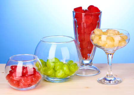 Color candies in glasses on wooden table on blue background photo