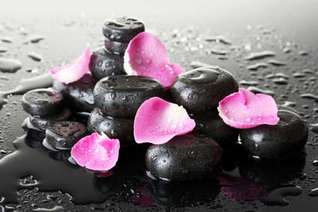 Spa stones with drops and rose petals on grey background photo