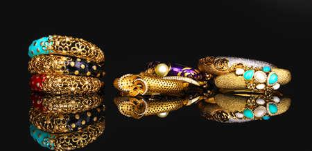 Beautiful golden bracelets isolated on black background photo