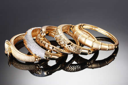 Beautiful golden bracelets on grey background Stock Photo - 14055309