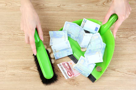 sweeps: Sweeps money in the shovel on wooden background close-up Stock Photo