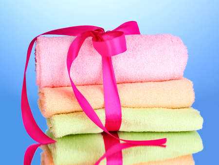Colorful towels with ribbon on blue background photo