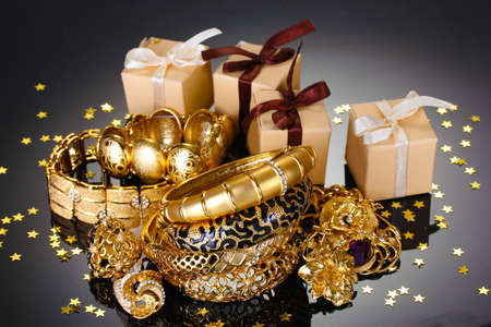 Beautiful golden jewelry and gifts on grey background photo