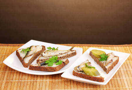 Tasty sandwiches with sprats on plate on wooden mat on brown background photo
