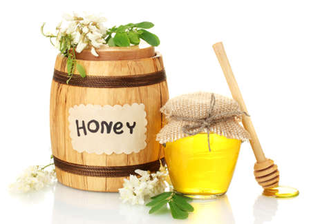 Sweet honey in barrel and jar with acacia flowers isolated on white photo